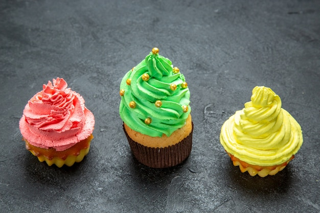 Vue de face de mini cupcakes colorés à rangée horizontale sur un espace libre de photo de noël sombre