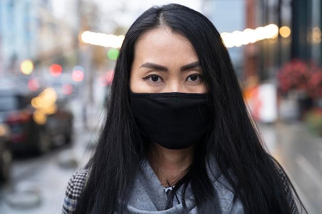 Vue de face modèle asiatique posant avec masque