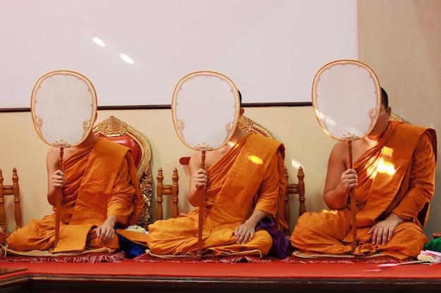 Vue de face des moines tenant un fan de talipot et priant sur le siège au temple.