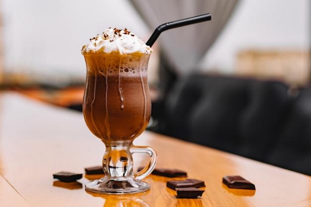 Vue de face mokachino avec crème fouettée et chocolat sur la table