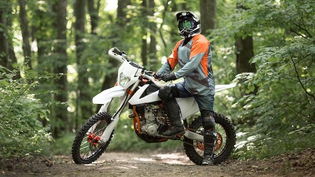 Vue de face moto rider posant dans la forêt