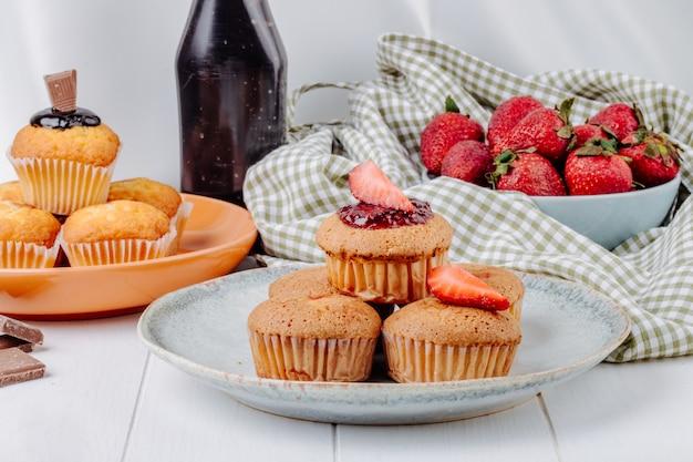 Vue de face muffins aux fraises et muffins au chocolat sur des assiettes aux fraises