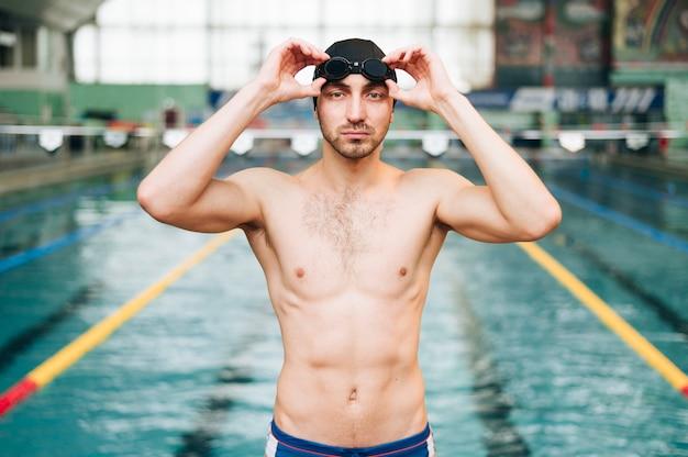 Vue de face d'un nageur mettant des lunettes de natation