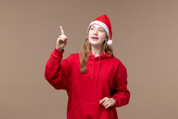 Vue de face noël fille pointant sur fond marron vacances nouvel an noël