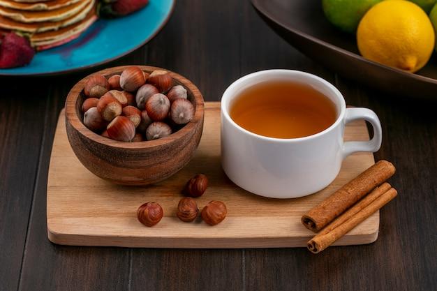 Vue de face de la noisette dans un bol avec une tasse de thé et de cannelle sur une planche sur une surface en bois