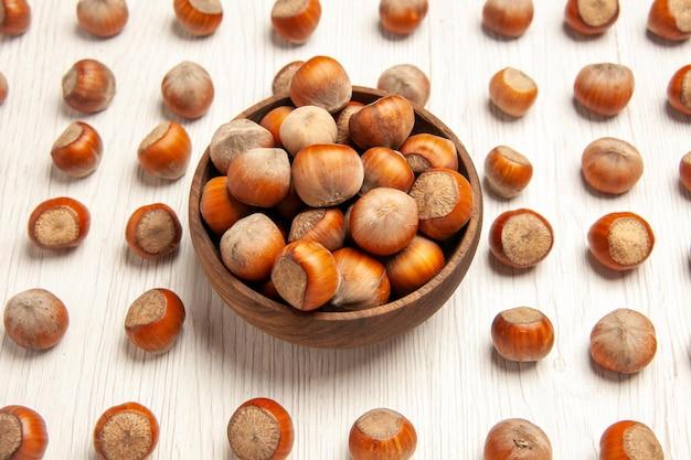 Vue de face de noisettes fraîches sur un bureau blanc écrou snack plante noix cacahuète