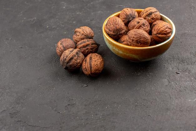 Vue de face des noix fraîches sur une surface sombre