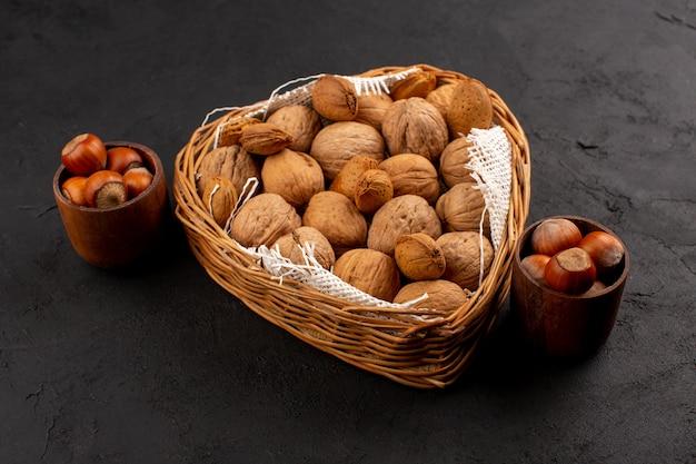 Vue de face noix et noisettes à l'intérieur du panier et pots marron sur le sol sombre