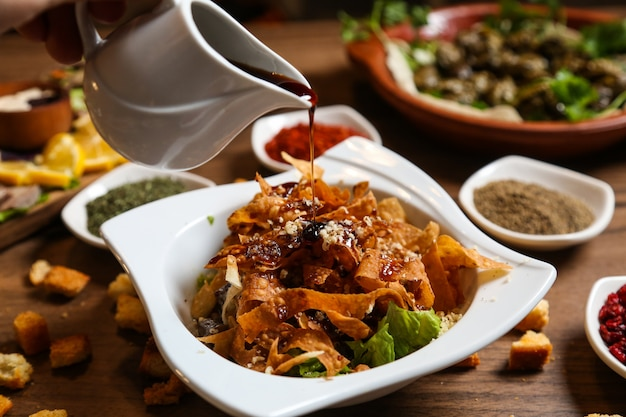 Vue de face nouilles frites avec sauce et croûtons sur la table