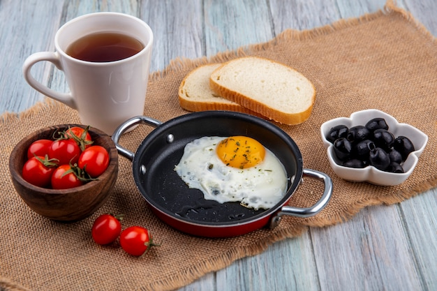 Vue de face de l'oeuf au plat dans la casserole avec bol de tomate et de thé avec des tranches de pain et bol d'olive sur un sac et une surface en bois