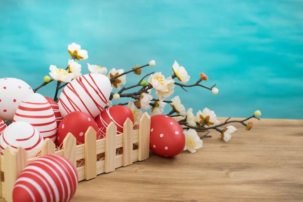 Vue de face d'un oeuf de pâques dans un panier et des fleurs de printemps sur fond de bois et turquoise avec espace message.