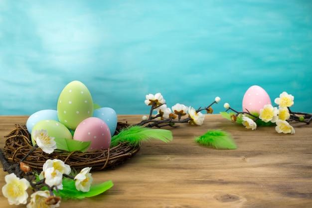 Vue de face d'un oeuf de pâques dans son nid, des plumes vertes et des fleurs de printemps sur fond de bois et turquoise avec espace de message.