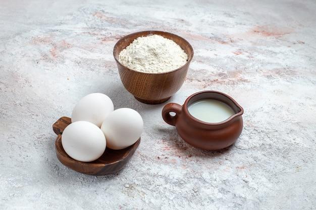 Vue de face des oeufs crus entiers avec de la farine et du lait sur la surface blanche des oeufs crus petit déjeuner repas