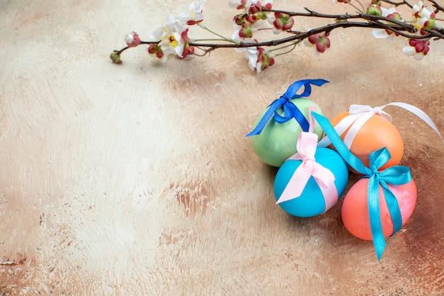 Vue de face des oeufs de pâques colorés attachés avec des arcs mignons sur une surface claire couleurs de pâques ethniques multi printemps vacances