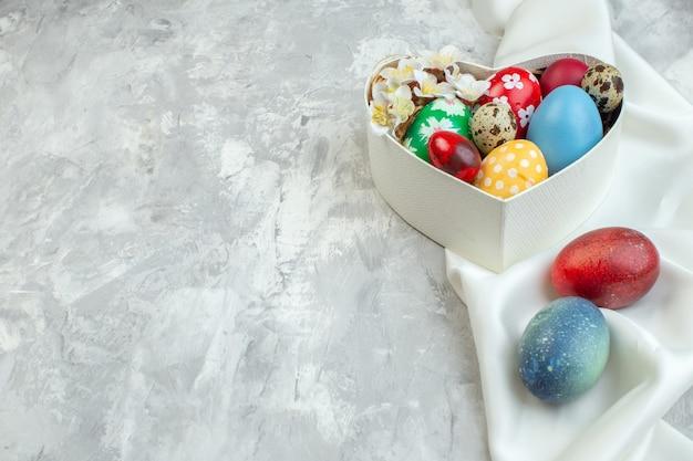Vue de face des oeufs de pâques colorés à l'intérieur d'une boîte en forme de coeur sur fond blanc concept de féminité orné de couleurs pâques de printemps