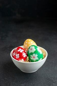 Vue de face des oeufs de pâques colorés à l'intérieur de la plaque sur fond sombre couleur concept printemps fleuri coloré