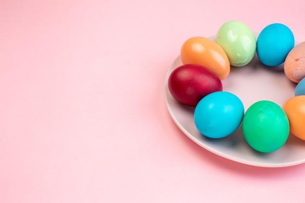Vue de face des oeufs de pâques colorés à l'intérieur de la plaque sur la surface rose vacances de printemps concept de couleur orné de couleurs pâques
