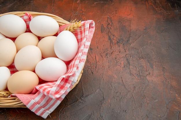 Vue de face des œufs de poule blancs à l'intérieur du panier avec une serviette sur la surface sombre