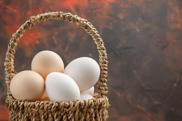 Vue de face des œufs de poule à l'intérieur du panier sur la surface sombre