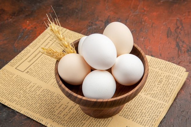 Vue de face des œufs de poule à l'intérieur de la plaque sur une surface sombre