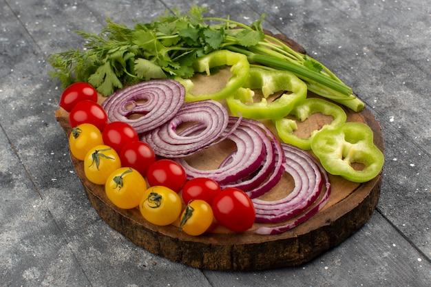 Vue de face oignons tomates poivron tranché et entier sur le front et gris