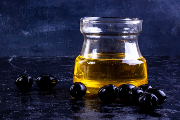 Vue de face des olives noires avec de l'huile d'olive dans un bocal en verre sur fond noir