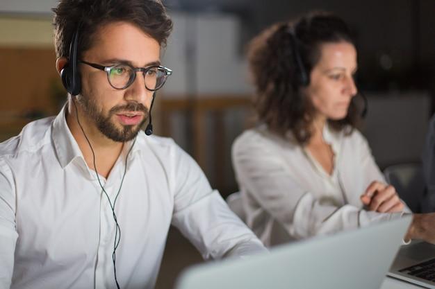 Vue de face de l'opérateur du centre d'appels communiquant avec le client