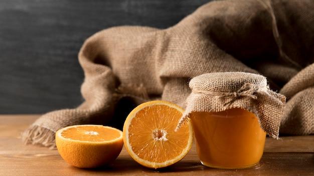 Vue de face des oranges et du pot de marmelade et de la toile de jute