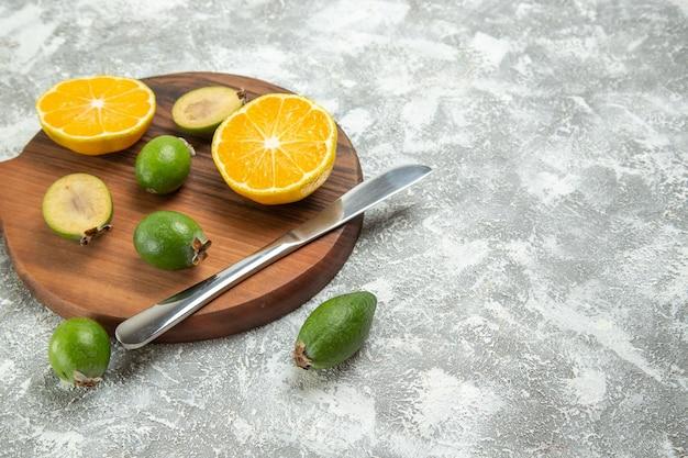 Vue de face oranges fraîches tranchées avec feijoa sur fond blanc fruits mûrs exotiques frais tropicaux