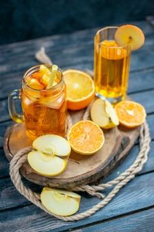 Vue de face des oranges et des pommes coupées en cocktail sur planche de bois dans l'obscurité