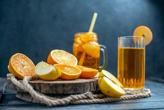 Vue de face des oranges et des pommes coupées en cocktail sur planche de bois sur fond isolé sombre