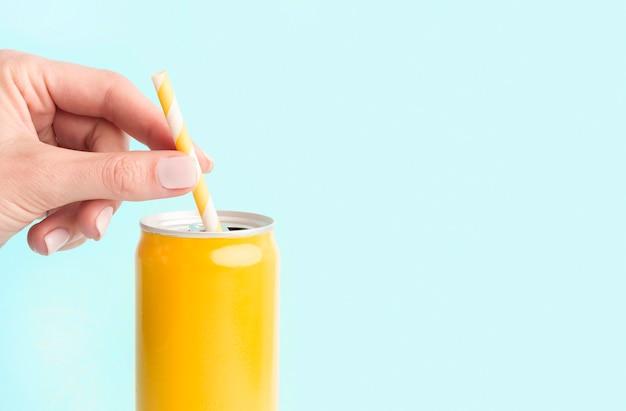 Vue de face de la paille à la main en canette de boisson gazeuse
