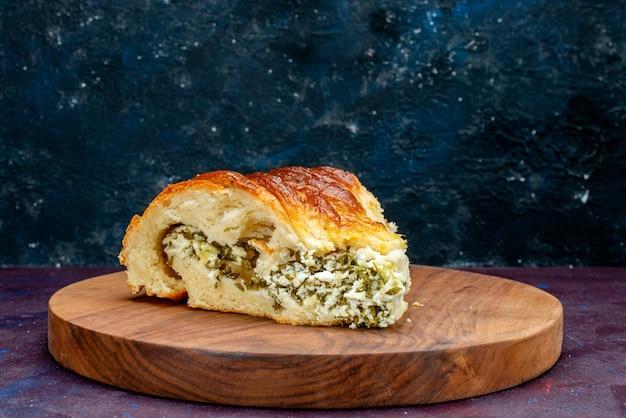 Vue de face de pain de pâtisserie cuit au four formé en tranches avec des verts à l'intérieur sur le fond sombre.