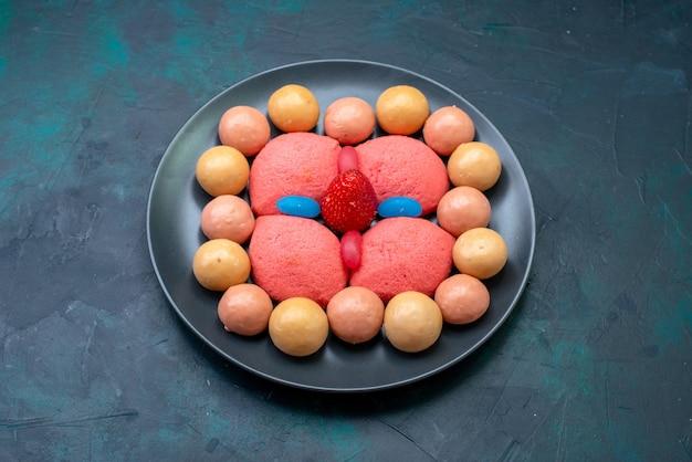 Vue de face de pains d'épices roses avec des bonbons sur un bureau sombre