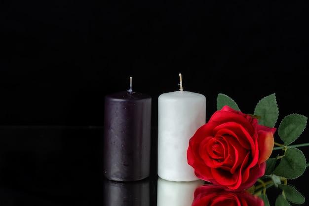 Vue de face d'une paire de bougies avec une rose rouge sur fond noir