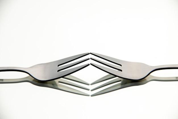 Vue de face paire de fourches avec reflet dans la surface