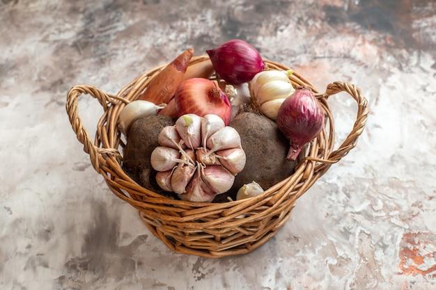 Vue de face panier avec légumes ails oignons et betteraves sur fond clair