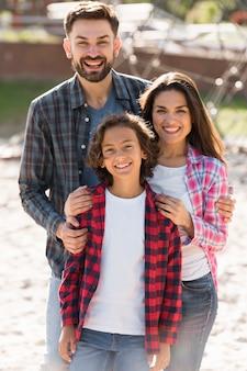 Vue de face des parents avec enfant posant à l'extérieur
