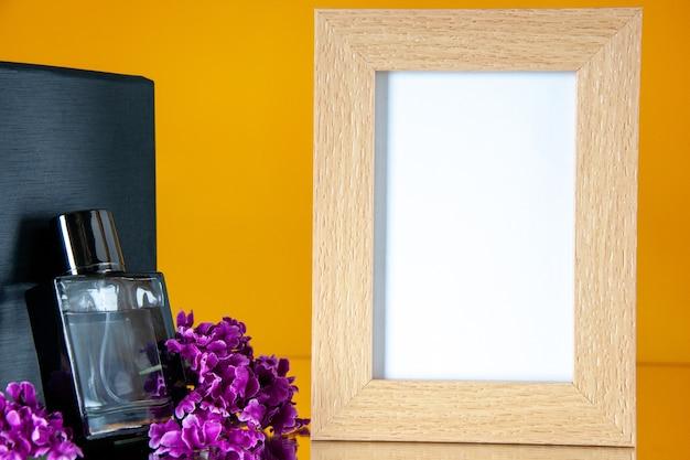 Vue de face parfum cher avec cadre photo sur fond orange parfum présent amour parfum valentines jour sentiment fleur portrait