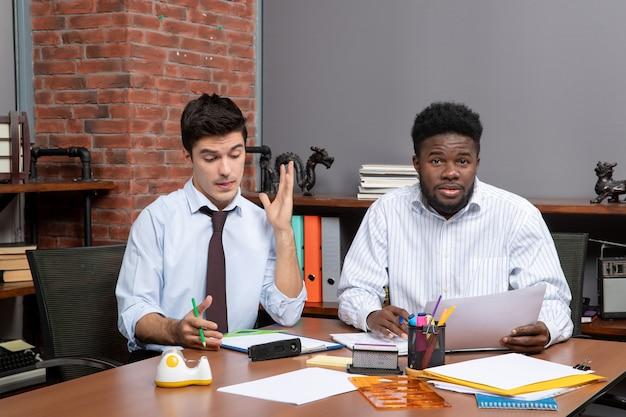 Vue de face des partenaires commerciaux assidus assis au bureau
