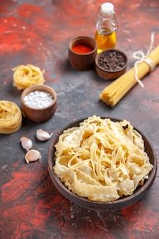 Vue de face de la pâte crue en tranches avec des assaisonnements sur la pâte à pâtes de surface sombre nourriture noire