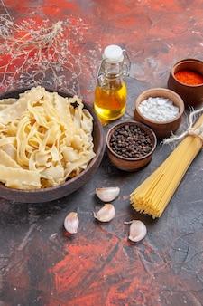 Vue de face de la pâte crue en tranches avec des assaisonnements sur des pâtes alimentaires de surface sombre pâte foncée