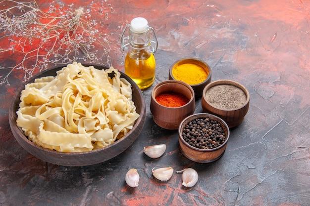 Vue de face de la pâte crue en tranches avec des assaisonnements sur la surface sombre de la nourriture de pâtes pâte foncée