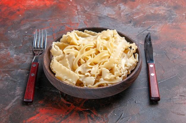 Vue de face de la pâte crue en tranches à l'intérieur de la plaque sur la surface sombre de la pâte de pâte alimentaire sombre