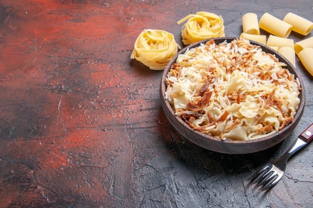 Vue de face de la pâte cuite en tranches avec du riz sur la pâte de pâtes repas plat surface sombre