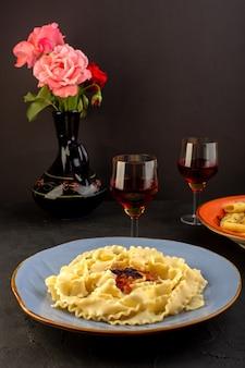 Une vue de face de pâtes cuites savoureuses salées à l'intérieur de la plaque bleue ronde avec des verres de vin et de fleurs à l'intérieur de la cruche sur tapis conçu et bureau sombre