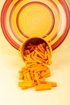Une vue de face des pâtes à l'intérieur du panier formé orange cru à l'intérieur du panier jaune sur le fond crème pâtes alimentaires repas