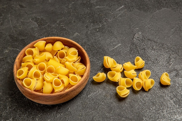 Vue de face des pâtes italiennes crues sur un espace gris