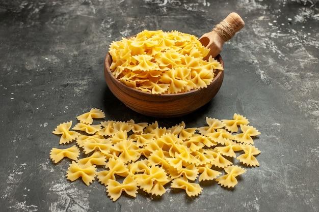 Vue de face des pâtes italiennes crues à l'intérieur de la plaque sur une photo de couleur gris foncé repas cuisine alimentaire