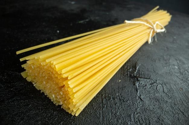 Vue de face des pâtes italiennes crues longtemps formées sur une photo de repas de couleur alimentaire à pâte foncée